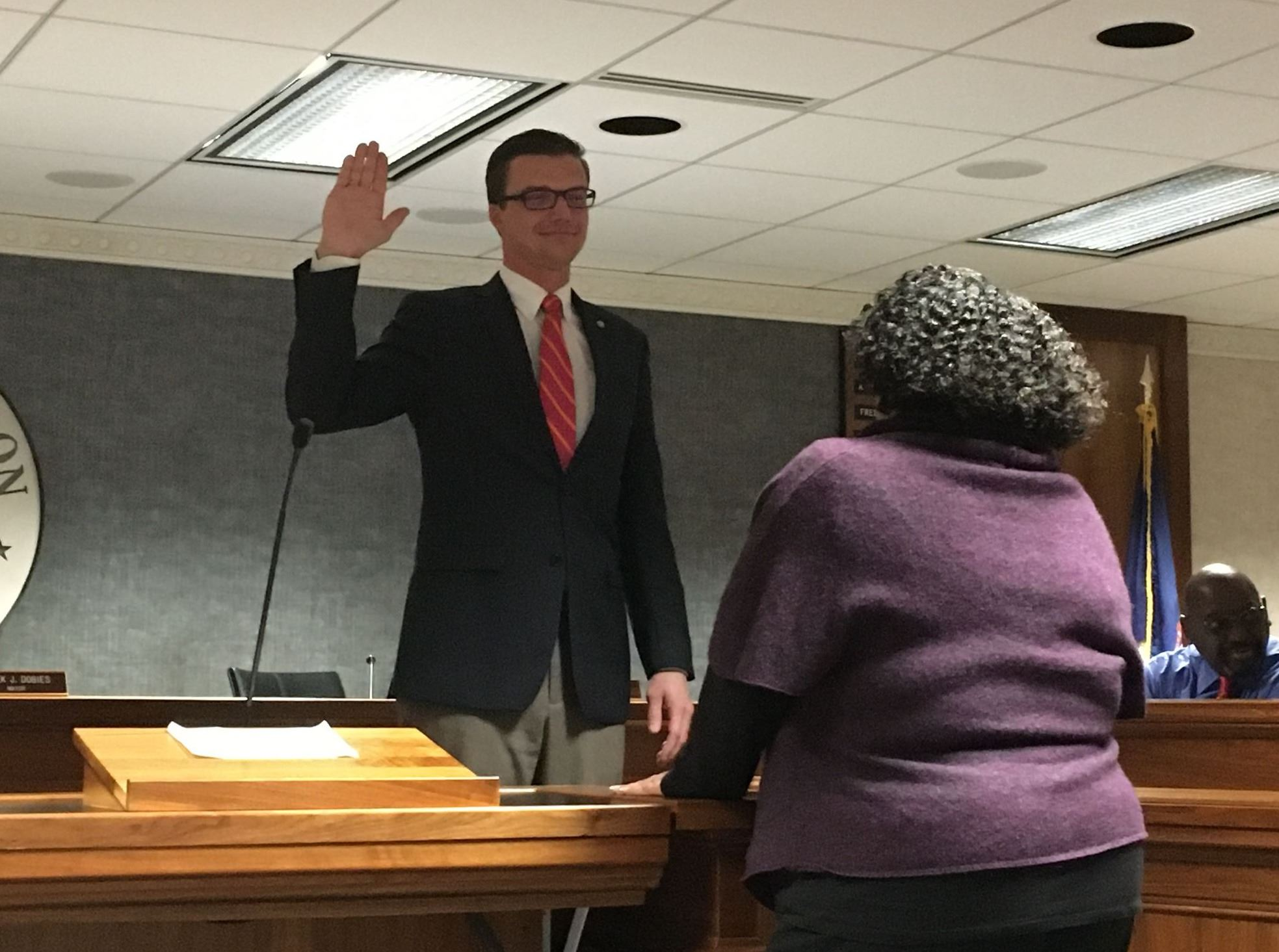 Mayor Derek Dobies with his hand up taking the oath of office