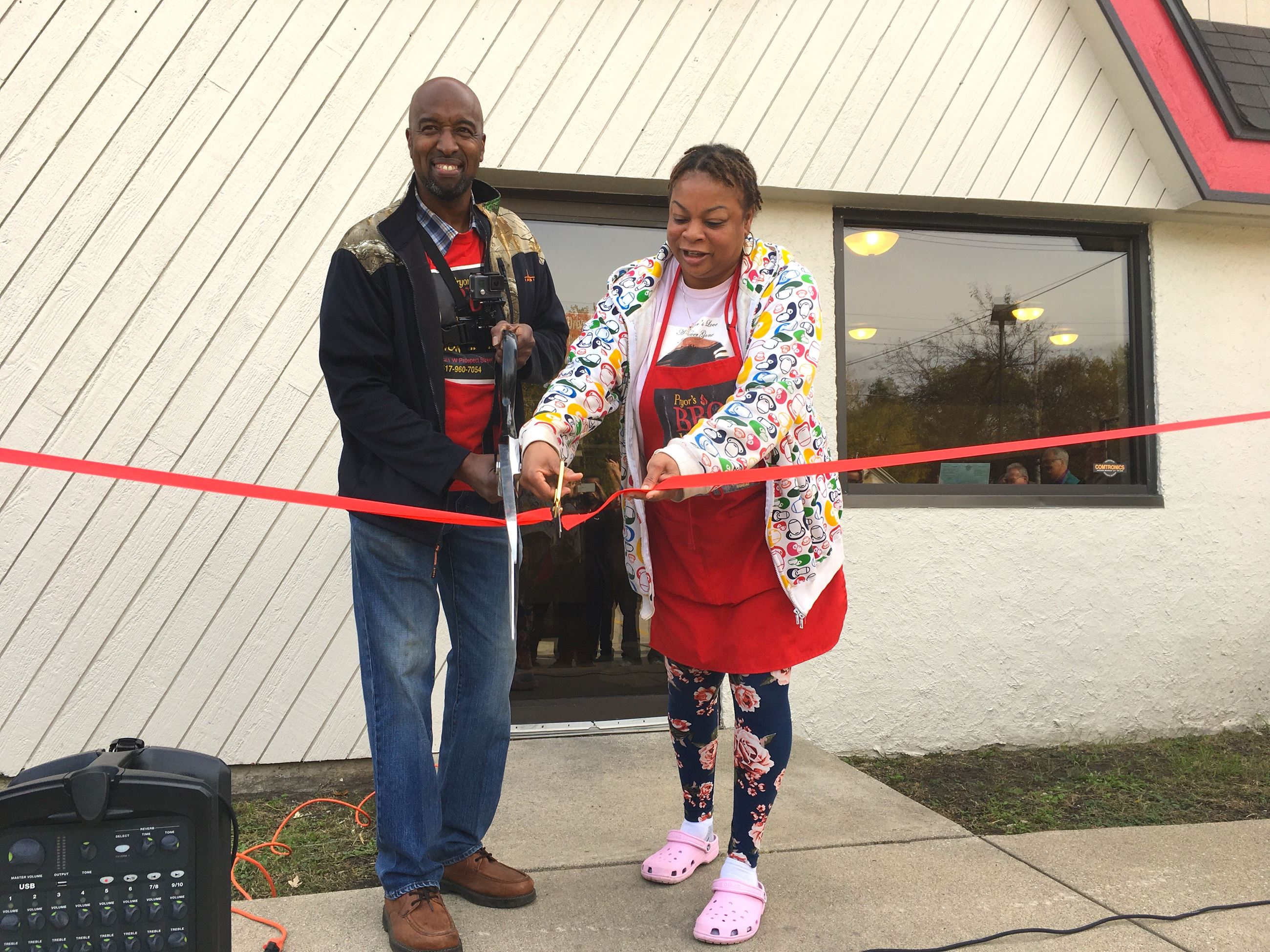 Larry and Stephanie Pryor cut the ribbon at a ribbon cutting ceremony in the fall