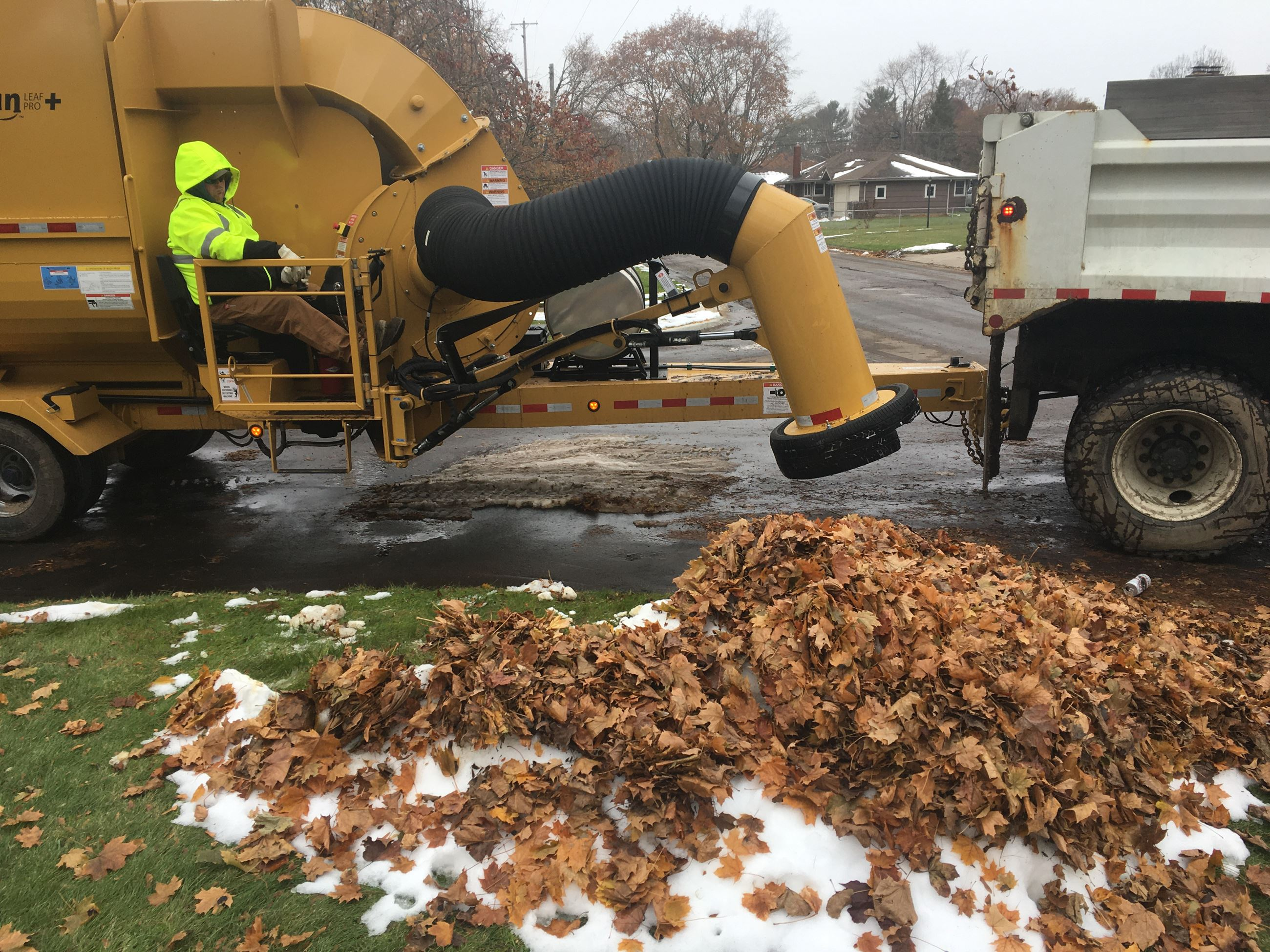 Leaf vacuum equipment gets ready to suck up a pile of leaves