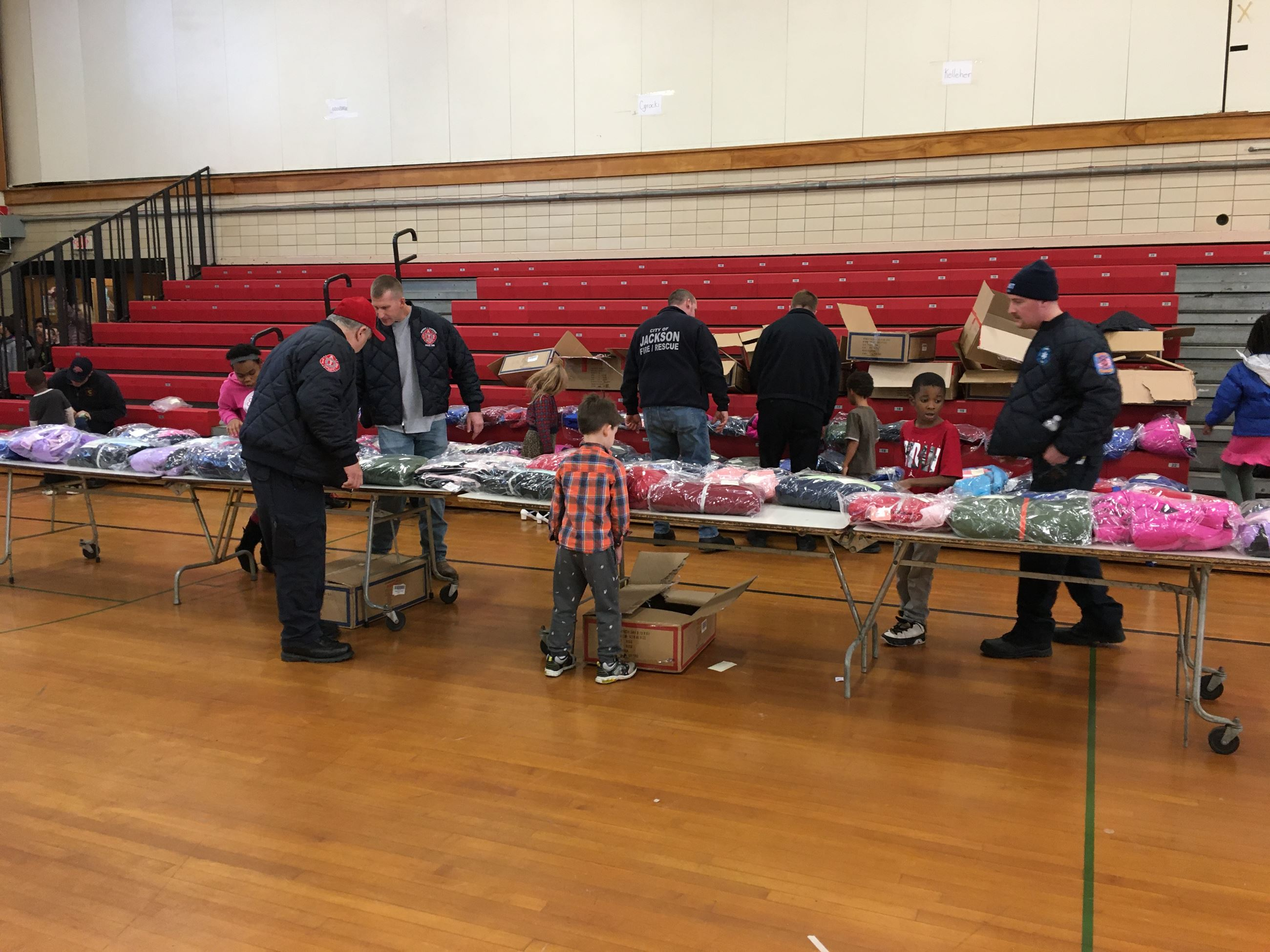 kids and firefighters look at coats on a table