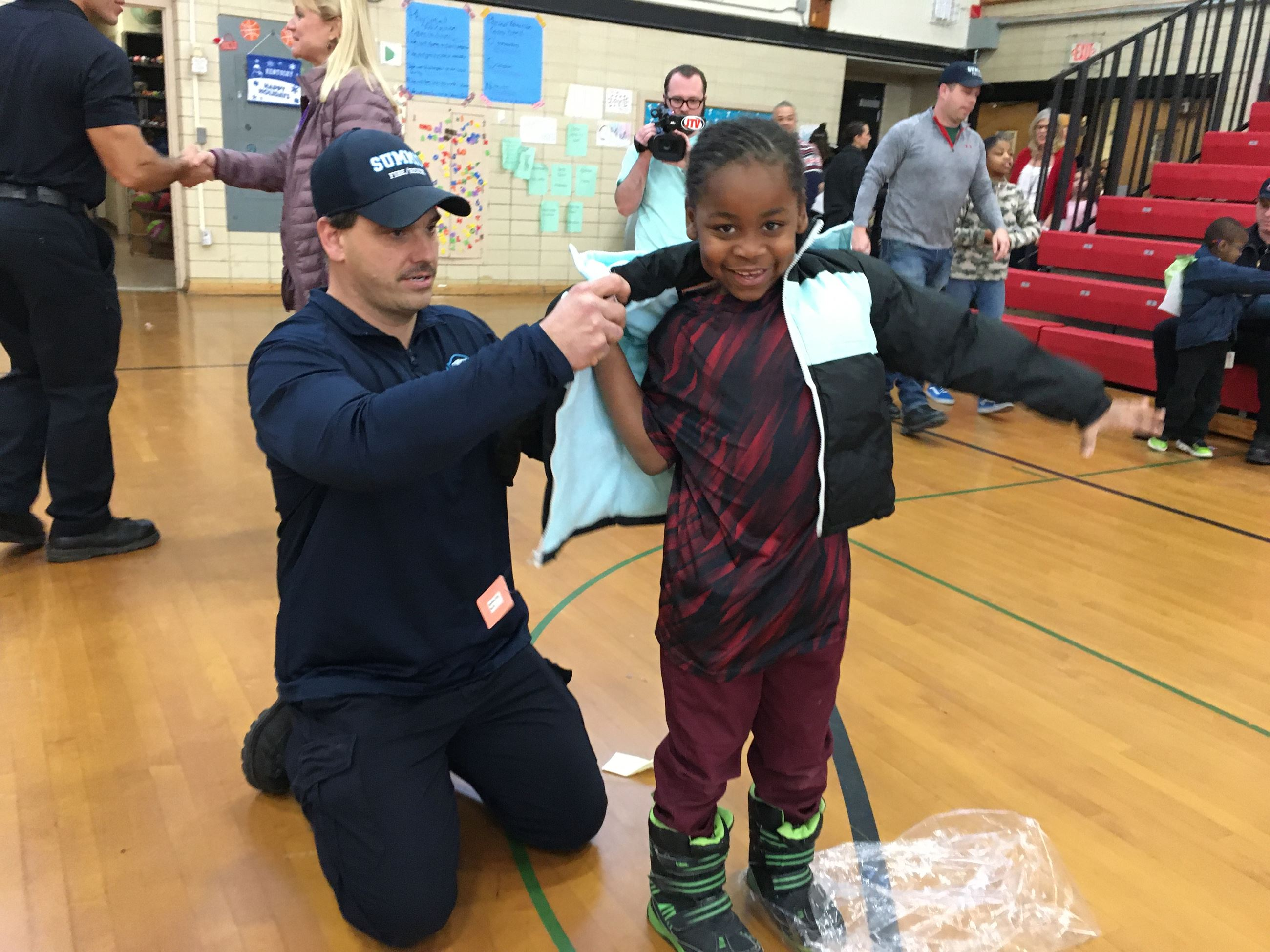 A little boy smiles as a firefighter helps him try on a coat