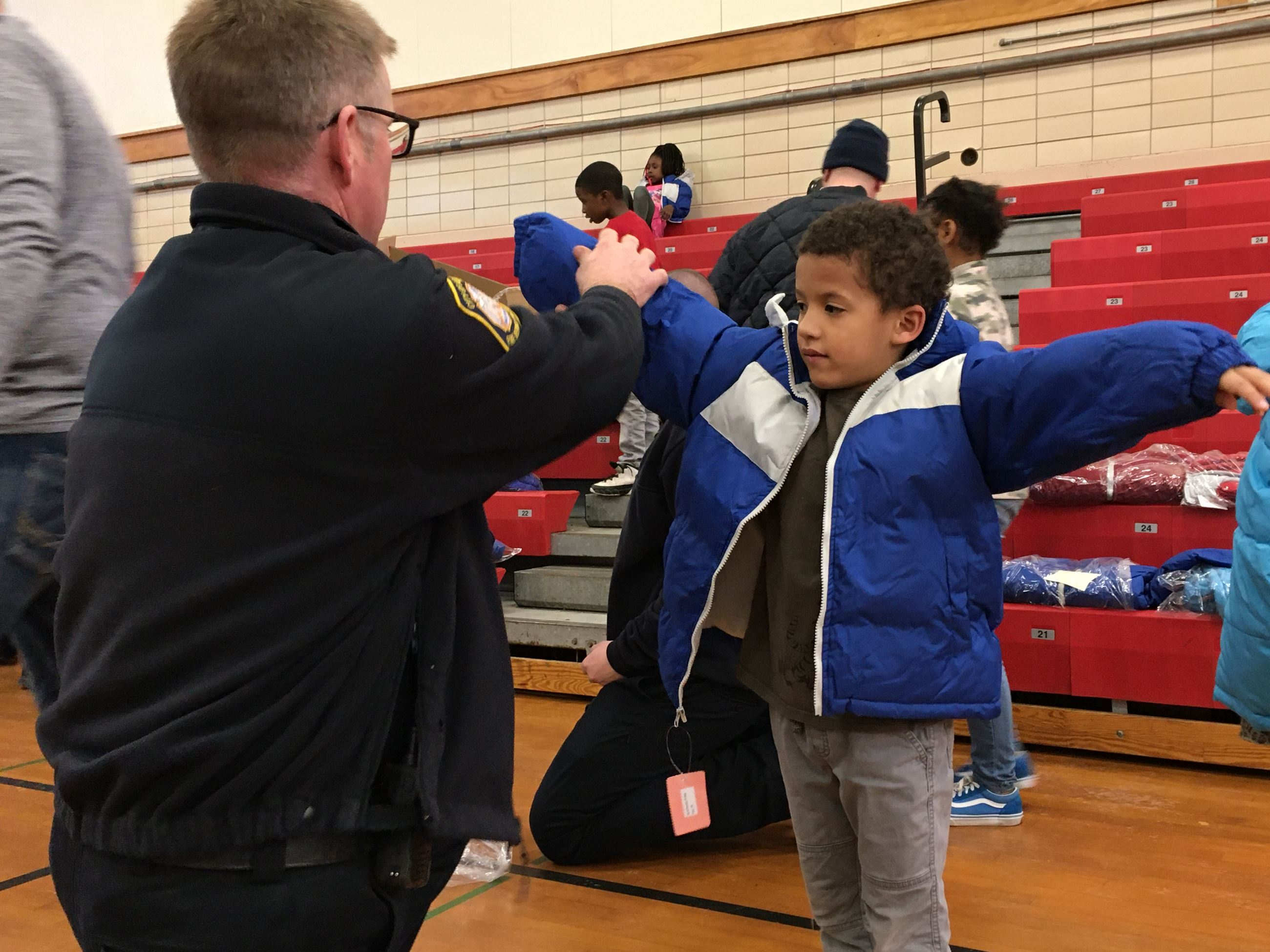 a firefighter helps a boy try on a coat